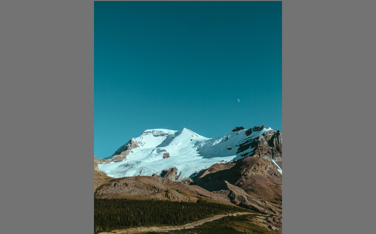 Epic mountain landscape with daytime moon on blue-green sky original photo by Ryan Schroeder