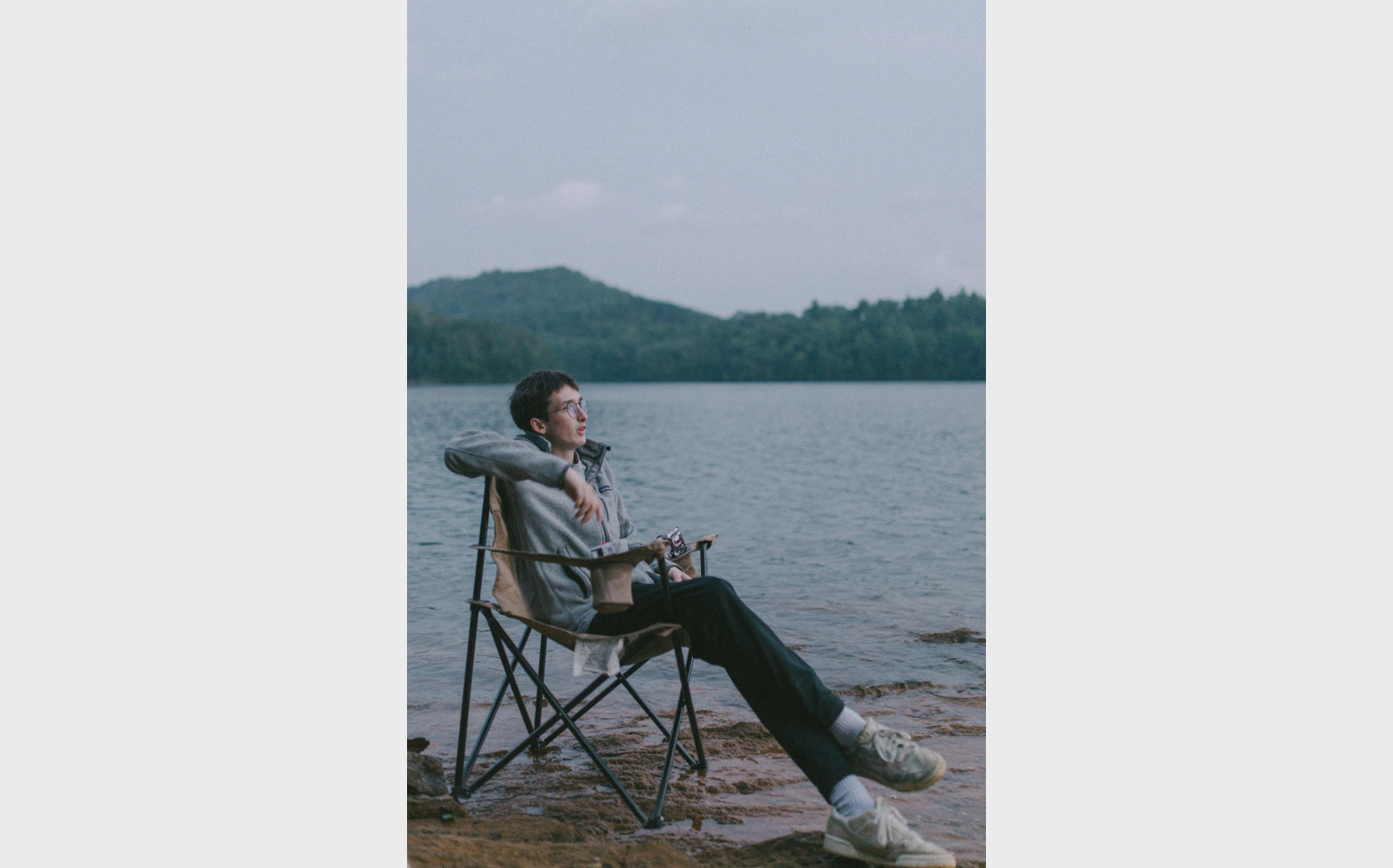 The guy in greyish clothes sitting in a camping chair by the lake original photo by Hunter Matthews