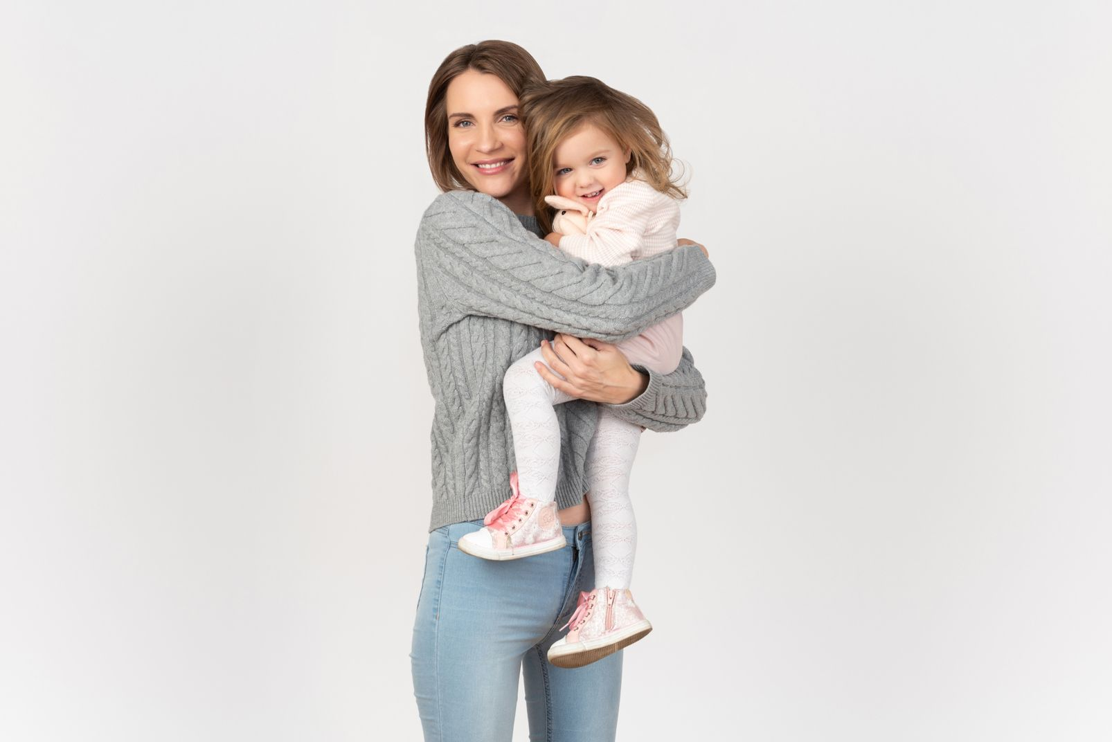 mom holds little daughter in her arms on gray background